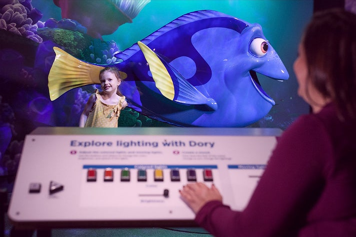 """Visitors adjust the lighting for their photo with Dory at """"The Science Behind Pixar"""""""